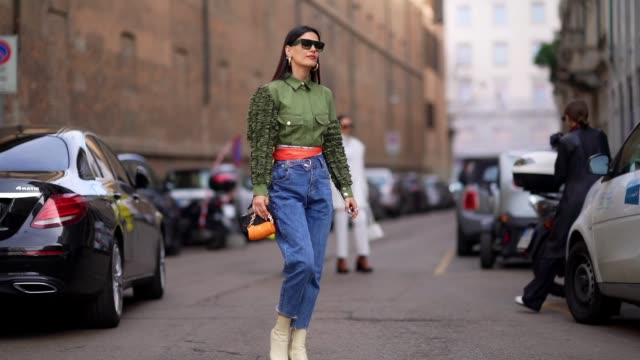 asena saribatur wears earrings, sunglasses, a green shirt with ruffled sleeves and pockets, an orange scarf around the waist, blue denim cropped... - jeans stock-videos und b-roll-filmmaterial