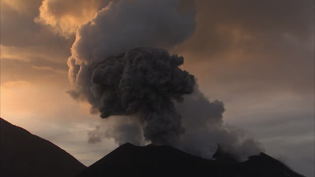ash billows from erupting volcano at sunrise, new britain, png - cenere video stock e b–roll