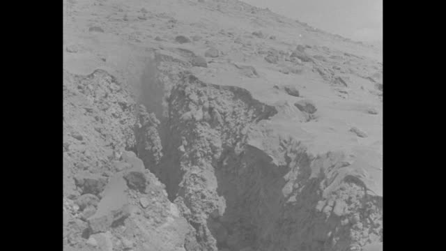 vs ash cloud erupts from top of mount asama and a jagged crevasse / vs villagers with possessions and small children in crates placed on either side... - 1930~1939年点の映像素材/bロール