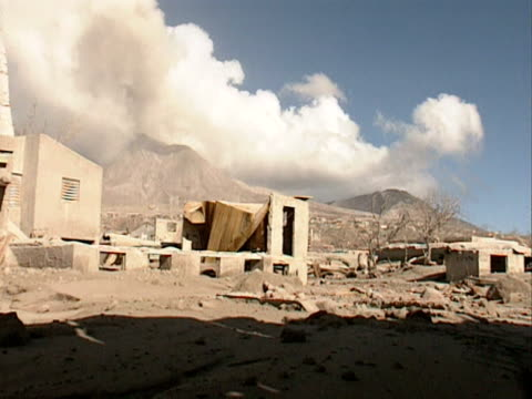 Ash clouds billow from the Sourfriere Hills volcano above the ruined town of Plymouth Montserrat 1998