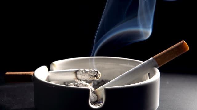 Ashtray with Burning Cigarettes against Black Background, Real Time