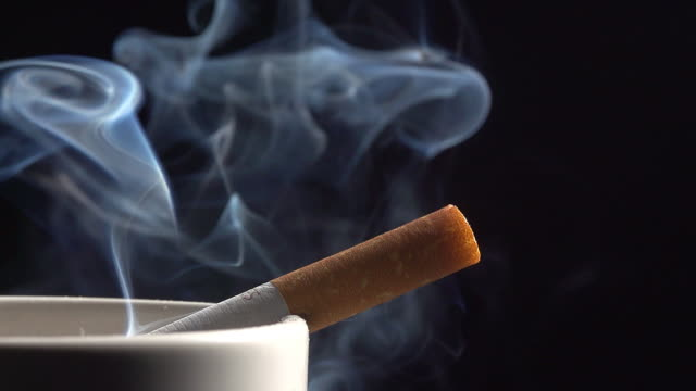 ashtray with smoking cigarette against black background, real time - sigaretta video stock e b–roll