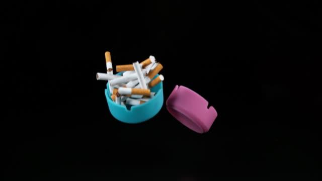 Ashtrays and Cigarettes Falling against Black Background, Slow Motion 4K