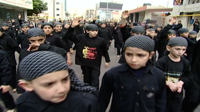 vidéos et rushes de ashura procession organized by hezbollah in dahieh boys raise their hands in salutation while walking barefoot the ashura commemorates the death of... - coiffe traditionnelle