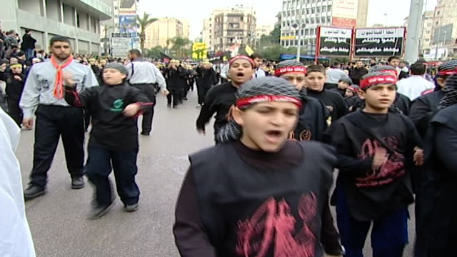 stockvideo's en b-roll-footage met ashura procession organized by hezbollah in dahieh. school boys are marching and performing ritual thumping of chest commemorating the death of... - hoofdtooi