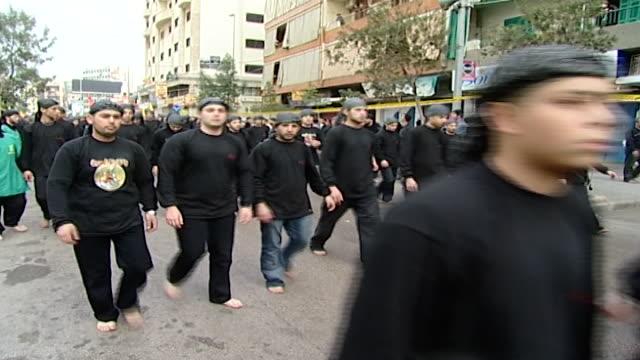 vídeos y material grabado en eventos de stock de ashura procession organized by hezbollah in dahieh. young men walking barefoot. the idea is to suffer as imam hussain did before his martyrdom. - ashura