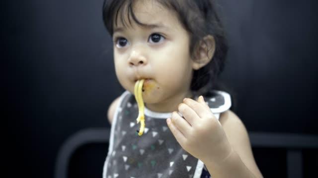 おいしい麺類を食べるアジアの赤ちゃん女の子 - 乱雑点の映像素材/bロール