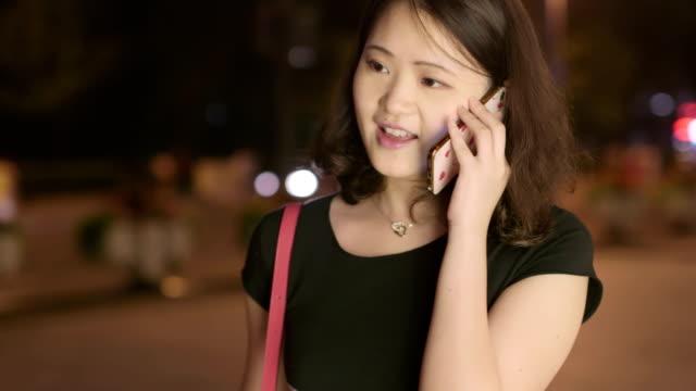 stockvideo's en b-roll-footage met asia mooi meisje praten over slimme telefoon 's nachts lopen straat. jonge vrouw praten over mobiele celtelefoon glimlachend gelukkig buitenshuis. - ingesproken bericht