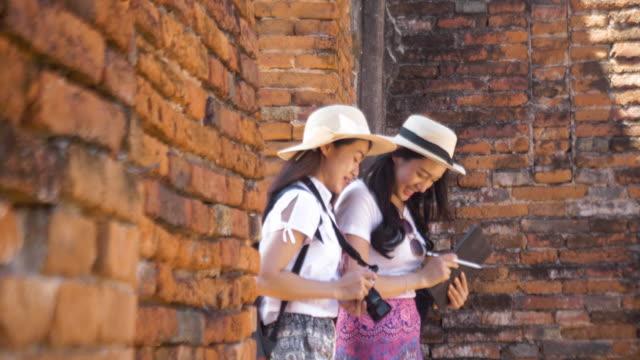 アジアの美女旅行者 アユタヤ、タイの寺院を探索しながら歩きながら写真を撮る。若い観光客の女性が歩き回り、古い古代の歴史建築、古い寺院、古い宮殿の景色を楽しんでいます - アユタヤ県点の映像素材/bロール