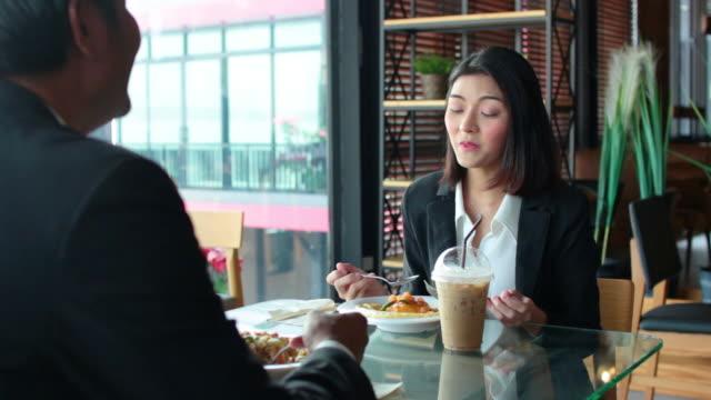 アジアのビジネスマンと女性は、レストランで昼食と一緒に食事を話します。ビジネスチームのグループは、パートナーにプロジェクトに関するアイデアを共有しています。 - 食事する点の映像素材/bロール