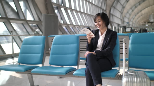 asia businesswoman using smart phone at airport - transportation building type of building stock videos & royalty-free footage