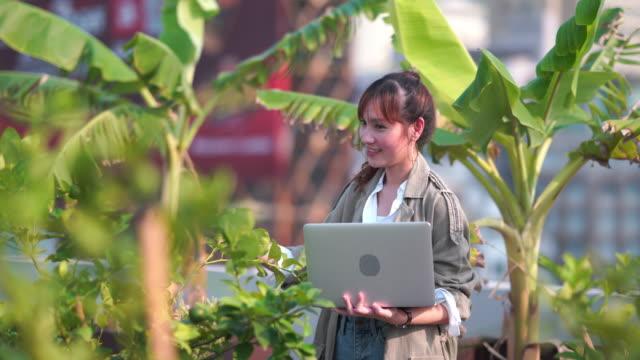 アジアのビジネスウーマンは、農業で人工知能と拡張現実を使用してシステムを成長させ、水を節約し、資源は労働時間を短縮します - グリーンハウス点の映像素材/bロール