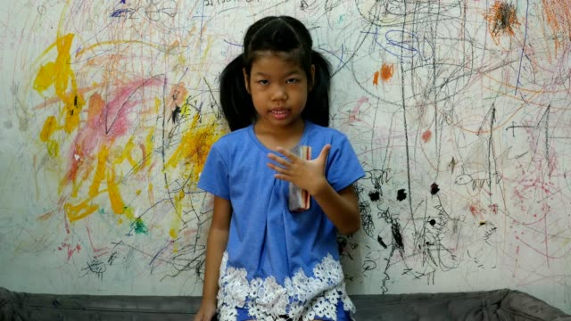 asia child stands in front of a painted wall. - only girls stock videos and b-roll footage