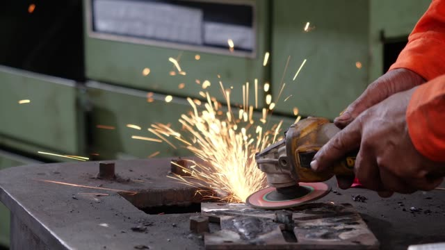 asia engineer and worker working in factory.close up factory workers are welding in protective helmets - metal worker stock videos & royalty-free footage