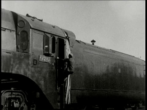 stockvideo's en b-roll-footage met asia express train that connects dairen and harbin engineer examines wheel climbs aboard engine people wave from platform conductor takes tickets... - 1938