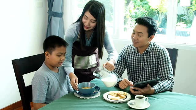 asia family have breakfast. the mother poured milk from the jug for the children and the father was drinking coffee. - milk jug stock videos & royalty-free footage