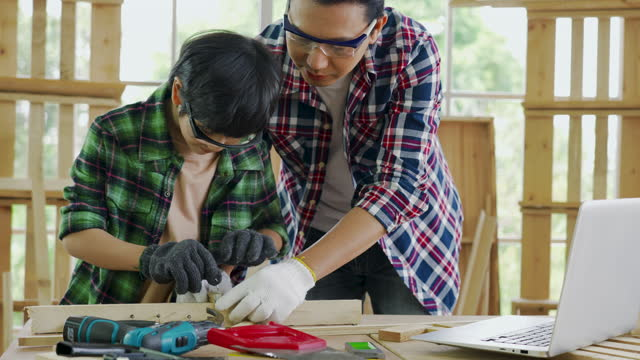 asia father and son share a common hobby in house.there is a lot of time to do carpentry. - wood material stock videos & royalty-free footage