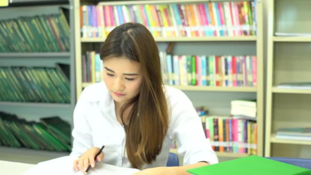 vídeos de stock, filmes e b-roll de aluna da ásia ler um livro na biblioteca da escola - óculos de leitura