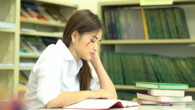 stockvideo's en b-roll-footage met asia vrouwelijke student lees een boek in de schoolbibliotheek - leesbril