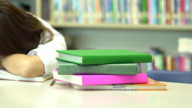 vídeos de stock, filmes e b-roll de aluna da ásia ler um livro na biblioteca da escola, enquanto seu sono e acorda - óculos de leitura