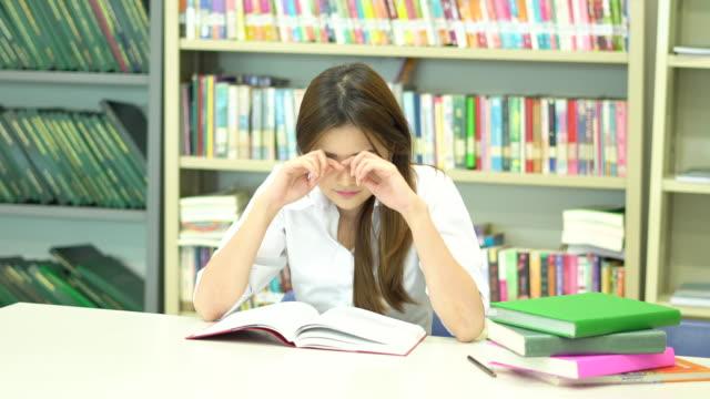 vídeos de stock, filmes e b-roll de aluna da ásia ler um livro na biblioteca da escola, enquanto ela vai dormir. - óculos de leitura