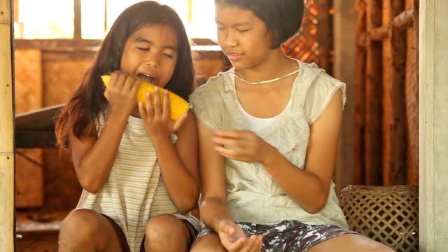 vídeos y material grabado en eventos de stock de asia chicas comiendo - maíz alimento