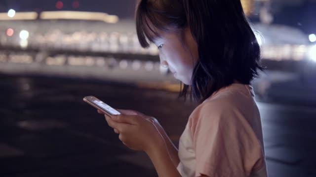 asia mädchen mit smartphone in der nacht. - nur mädchen stock-videos und b-roll-filmmaterial
