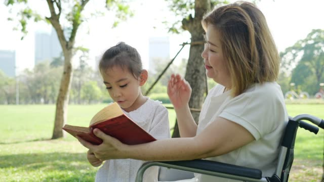 vidéos et rushes de petite-fille d'asie et grand-mère lisant le livre au parc. ralenti - chaise roulante