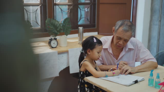asia grandfather teaching granddaughter do homework - prevenzione delle malattie video stock e b–roll