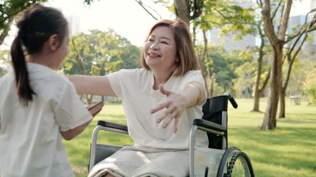 vidéos et rushes de grand-mère d'asie étreignant la petite-fille au parc. ralenti - chaise roulante