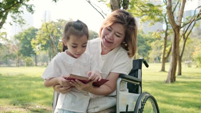 vidéos et rushes de asie grand-mère assis sur fauteuil roulant écouter petite-fille lire le livre au parc. ralenti - chaise roulante