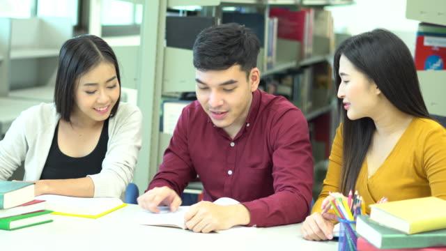 vídeos de stock, filmes e b-roll de estudante do grupo ásia ler um livro na biblioteca da escola - óculos de leitura