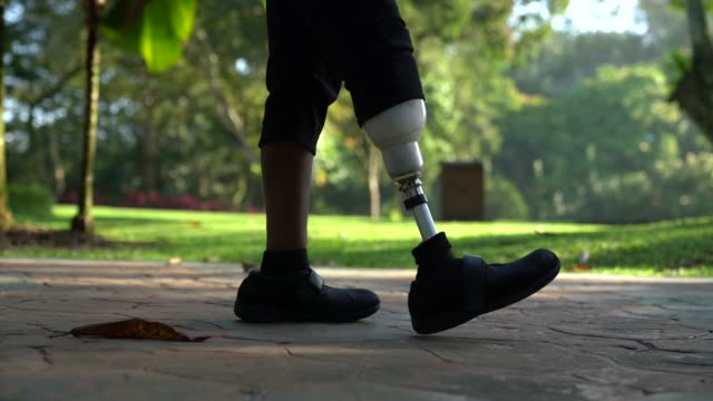 asia indian female amputee with prosthetic leg walking at public park - artificial limb stock videos & royalty-free footage