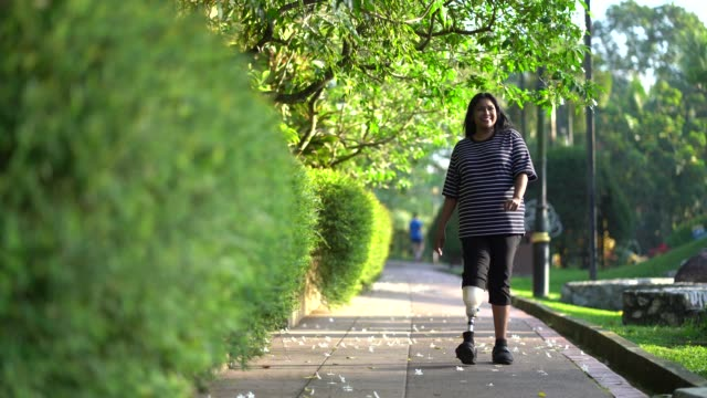 asia indian female amputee with prosthetic leg walking at public park - full length stock videos & royalty-free footage