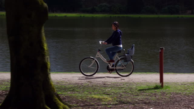 asia lady riding bike in forest - utrecht stock videos & royalty-free footage