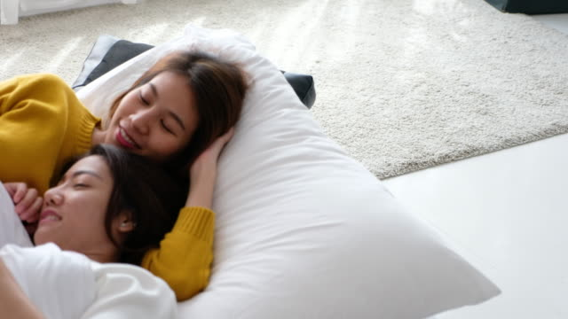 asia lesbian lgbt couple hugging lay on bed and use mobile phone together with happiness moment,love wins concept - human rights stock videos and b-roll footage