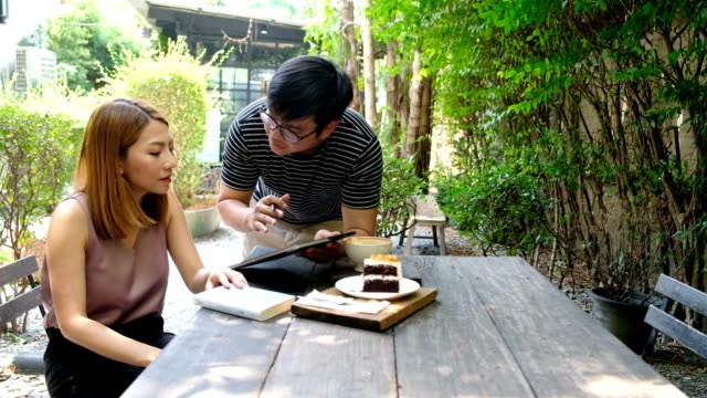 a asia man offering for sale something to woman who sit in coffee cafe . two freelance discuss on thair work - laptop remote location stock videos & royalty-free footage
