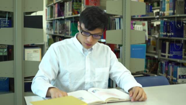 stockvideo's en b-roll-footage met asia man student lees een boek in de schoolbibliotheek - leesbril