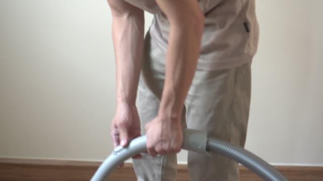 アジアの男性は、部屋や家をきれいにするために掃除機を使用しています - 掃除機点の映像素材/bロール