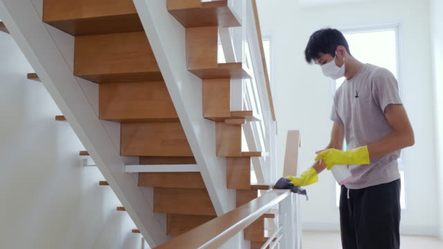 vídeos de stock e filmes b-roll de asia man wear yellow gloves for cleaning and disinfect covid-19 virus inside the house - limpo