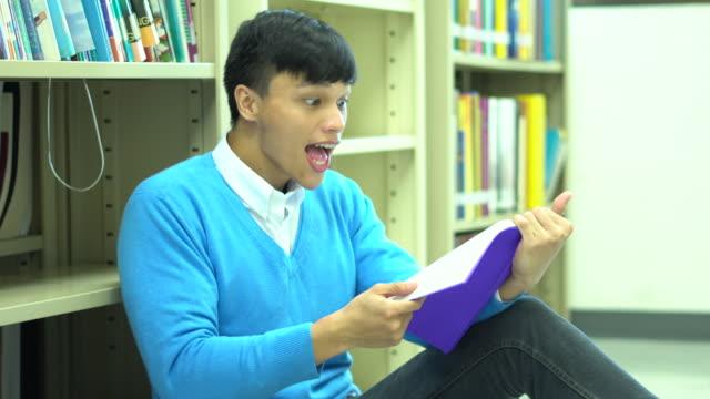 vidéos et rushes de élève moyen asie lire correctement un livre dans la bibliothèque de l'école - littérature