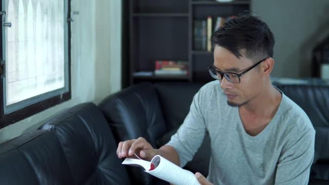 居間で本を読むアジアの男性 - 集中点の映像素材/bロール