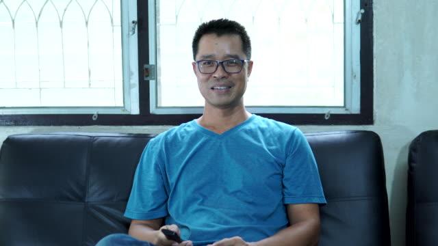 テレビを見ているアジアの男性 - テレビのリモコン点の映像素材/bロール