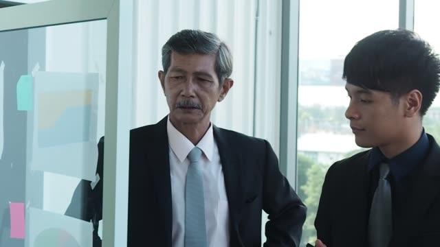 asia senior businessman and rookie businessman working together. senior businessman teaches stressful work - teaching stock videos & royalty-free footage