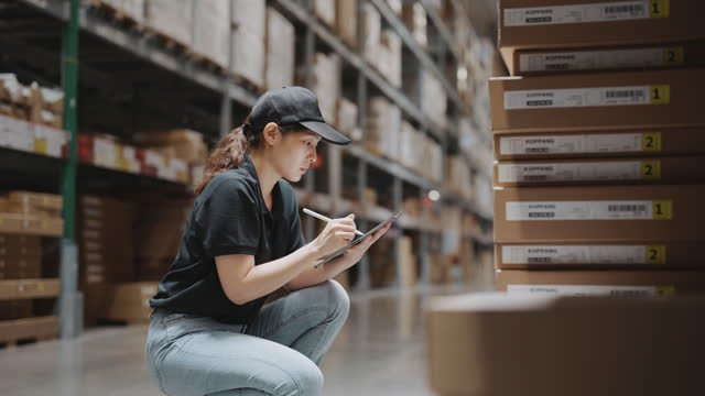 asia warehouse worker using digital tablet checking inventory levels standing in warehouse - achievement stock videos & royalty-free footage
