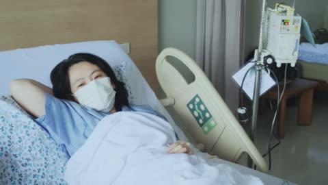 vidéos et rushes de femme d'asie une toux et malade avec le masque sur le lit de patient. - rétablissement