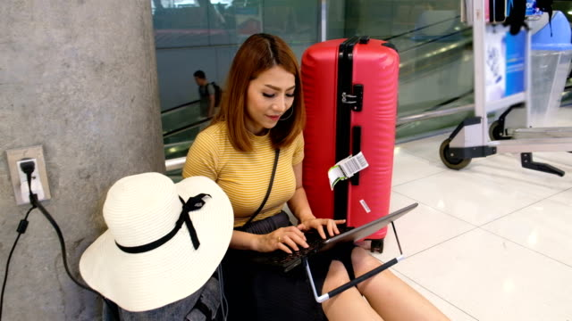 asia woman charging laptop and doing her work online in airport terminal - plug socket stock videos & royalty-free footage