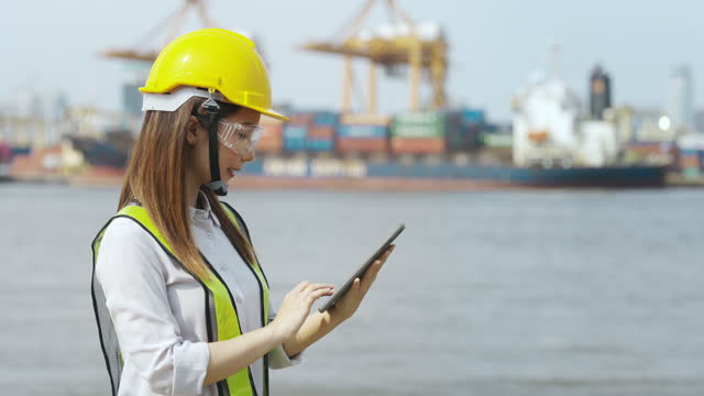 asia woman engineer using digital tablet working at construction site or shipyard background for construction or shipping industry concept. - construction worker stock videos & royalty-free footage