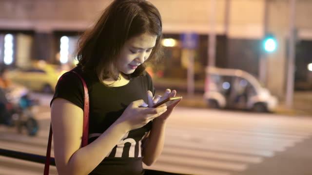 stockvideo's en b-roll-footage met vrouw asia sms-berichten met behulp van app op smartphone 's nachts in de stad. mooie jonge meisje met smartphone glimlachend gelukkig buitenshuis. - ingesproken bericht