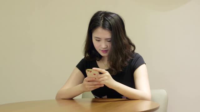 stockvideo's en b-roll-footage met vrouw asia sms-berichten met behulp van de app op de smartphone. mooie jonge meisje met smartphone in het hotel. - ingesproken bericht